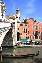 Venice, Italy:  A gondola glides under the Rialto Bridge on the Grand Canal.