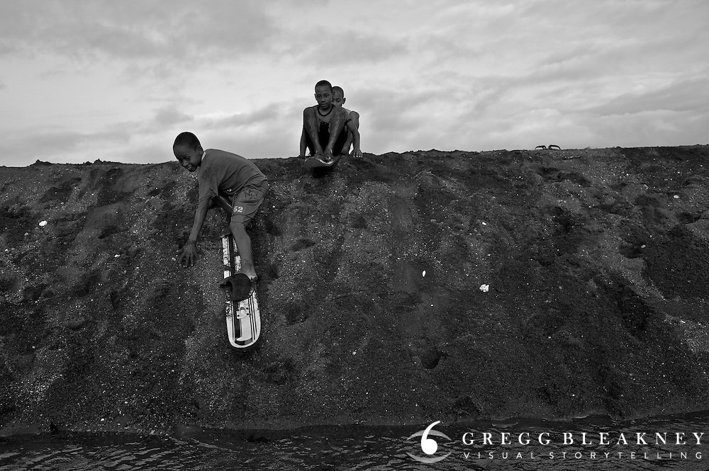 Boys play on old water skies - Pacific Coast - Colombia
