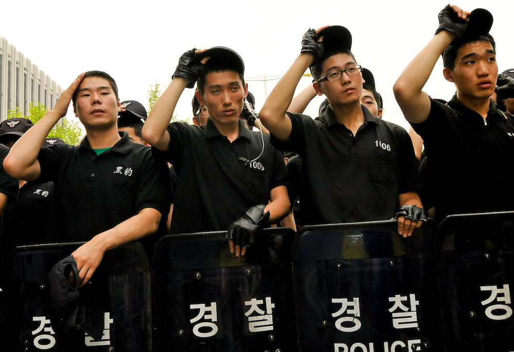 Police wipe sweat from their foreheads while guarding government property during a demonstration against the government of President Lee Myung-bak and the import of US beef in Seoul, South Korea.
