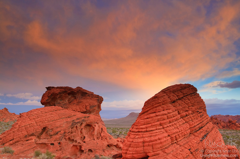 Red clouds lit by the sunrise seem to swarm from the fossilized sand dunes known as the Beehives in the Valley of Fire State Park, Nevada. The dunes were formed by a proccess known as aeolian erosion.