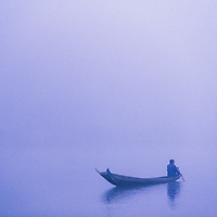 Fisherman paddling fishing boat in early morning mist, Ban Pak Ou, Luang Phrabang, Laos