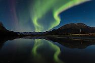 Aurora reflected on Portage Creek along Turnagain Arm in Southcentral Alaska. Autumn. Evening.