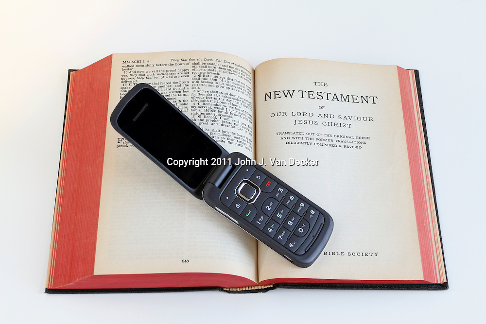A cell phone laying on a Bible opened to the New Testament. Communication and religion in the modern age.