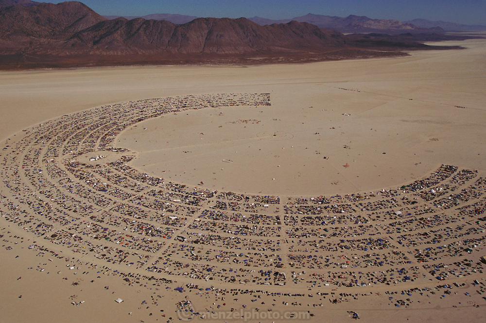 Black Rock Desert, Nevada.An early morning aerial of the Burning Man encampment on Nevada's Black Rock Desert. Over 20 thousand celebrants are camped around the 50-foot tall figure called Burning Man. The weeklong experiment in freewheeling community living, avant-garde art performance, and costumery (also drugs and sex), culminates with the Saturday night burning of the man. Burning Man Festival, Black Rock Desert, Nevada.