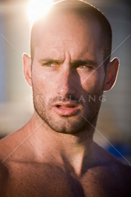 portrait of man with facial hair and a shaved head in sunset light