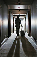 Rear view of man walking with his suit case in hotel