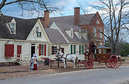 Williamsburg, VA, USA --  January 9, 2019. Photo of horses, carriage and drivers in period costume by a hitching post in Colonial Williamsburg.