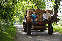 Two boys (5-6 7-9) sitting on back of trailer on country lane