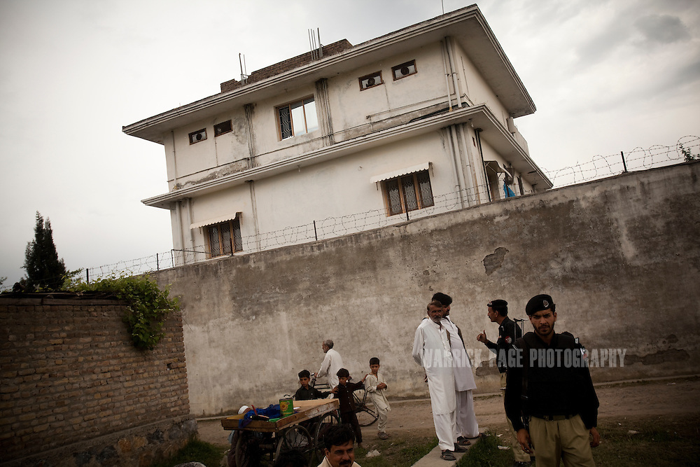 Locals and police gather outside the compound where Osama Bin Laden was reportedly killed in an operation by US Navy Seals, on May 3, 2011, in Abottabad, Pakistan. The operation, code-named Operation Neptune Spear, was launched from neighbouring Afghanistan by Seal Team Six. U.S. forces took bin Laden's body to Afghanistan for identification, then dumped it the Arabian Sea. Pakistan has since been widely suspected as having prior knowledge of his whereabouts as the compound was less than a kilometre from the country's biggest military academy. Osama bin Laden was allegedly responsible for supporting the bombing of the US Embassy in Nairobi, Kenya, the attack on the USS Cole and the suicidal attacks of September 11, 2001 in the US. (Photo by Warrick Page)