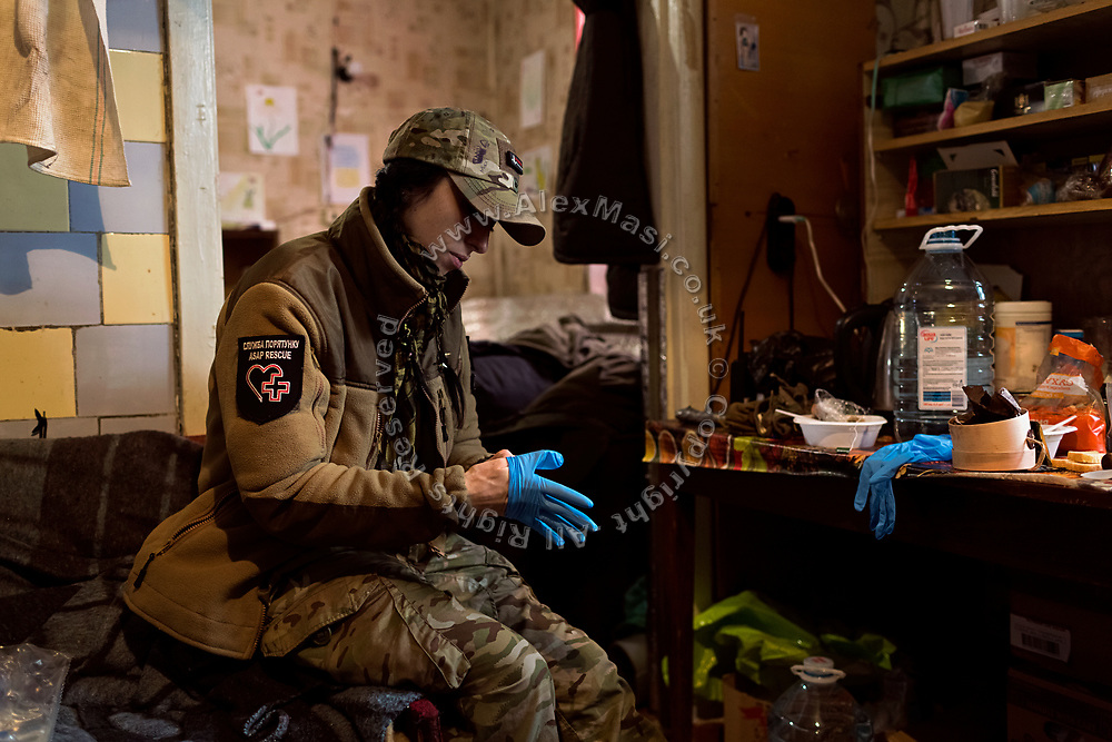 Elena Mosiychuk, (nom the guerre Maliok, or 'Baby') a member of ASAP, is wearing her surgical gloves while seating in an improvised 'warehouse' for medicines, set up in an abandoned home in the village of Klynove, near the frontline in eastern Ukraine.