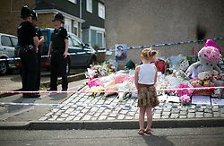 © Licensed to London News Pictures. 11/08/2012 . A young girl standing in front of flowers left at the end of  The Lindens, New Addington where a body was discovered in the hunt for missing 12 year-old schoolgirl Tia Sharp. Photo credit : LNP