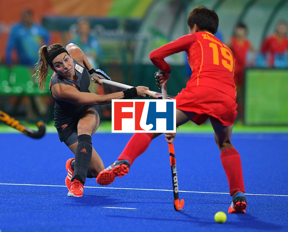 Netherland's Eva de Goede (L) plays a shot past China's Zhang Xiaoxue during the women's field hockey China vs Netherlands match of the Rio 2016 Olympics Games at the Olympic Hockey Centre in Rio de Janeiro on August, 10 2016. / AFP / Carl DE SOUZA        (Photo credit should read CARL DE SOUZA/AFP/Getty Images)
