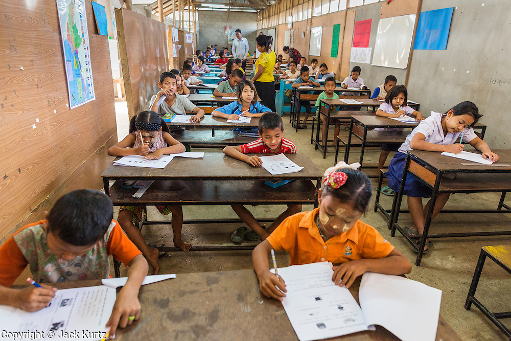 04 MARCH 2014 - MAE SOT, TAK, THAILAND: Students in the main classroom at the Sky Blue School. There are approximately 140 students in the Sky Blue School, north of Mae Sot. The school is next to the main landfill for Mae Sot and serves the children of the people who work in the landfill. The school relies on grants and donations from Non Governmental Organizations (NGOs). Reforms in Myanmar have alllowed NGOs to operate in Myanmar, as a result many NGOs are shifting resources to operations in Myanmar, leaving Burmese migrants and refugees in Thailand vulnerable. The Sky Blue School was not able to pay its teachers for three months during the current school year because money promised by a NGO wasn't delivered when the NGO started to support schools in Burma. The school got an emergency grant from the Burma Migrant Teachers' Association and has since been able to pay the teachers.    PHOTO BY JACK KURTZ
