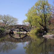 A tranquil scene as people relax beside a lake during a warm spring day in Central Park, Manhattan, New York, USA. Photo Tim Clayton