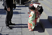 Japanese mother preparing little child for a photo during her Shichi Go San celebration