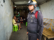 15 AUGUST 2016 - BANGKOK, THAILAND: A Thai police officer stands in the entrance of the Pom Mahakan slum when city officials issued eviction notices to the slum's residents. Final eviction notices were posted today and residents of the slum have been told they must leave the fort by September 3, 2016. The Pom Mahakan community is known for fireworks, fighting cocks and bird cages. Mahakan Fort was built in 1783 during the reign of Siamese King Rama I. It was one of 14 fortresses designed to protect Bangkok from foreign invaders. Only two of the forts are still standing, the others have been torn down. A community developed in the fort when people started building houses and moving into it during the reign of King Rama V (1868-1910). The land was expropriated by Bangkok city government in 1992, but the people living in the fort refused to move. In 2004 courts ruled against the residents and said the city could take the land.      PHOTO BY JACK KURTZ
