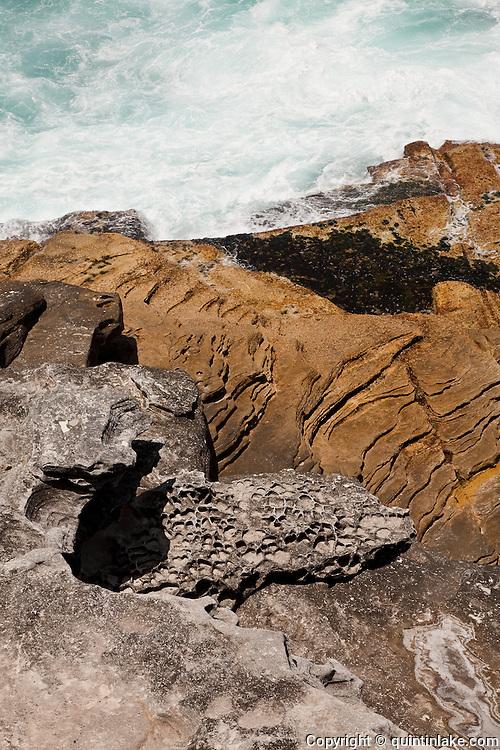 Waves break over the rocks at Mackenzies bay seen from the path on the Coogee to Bondi beach Coastal walk , Sydney, Australia