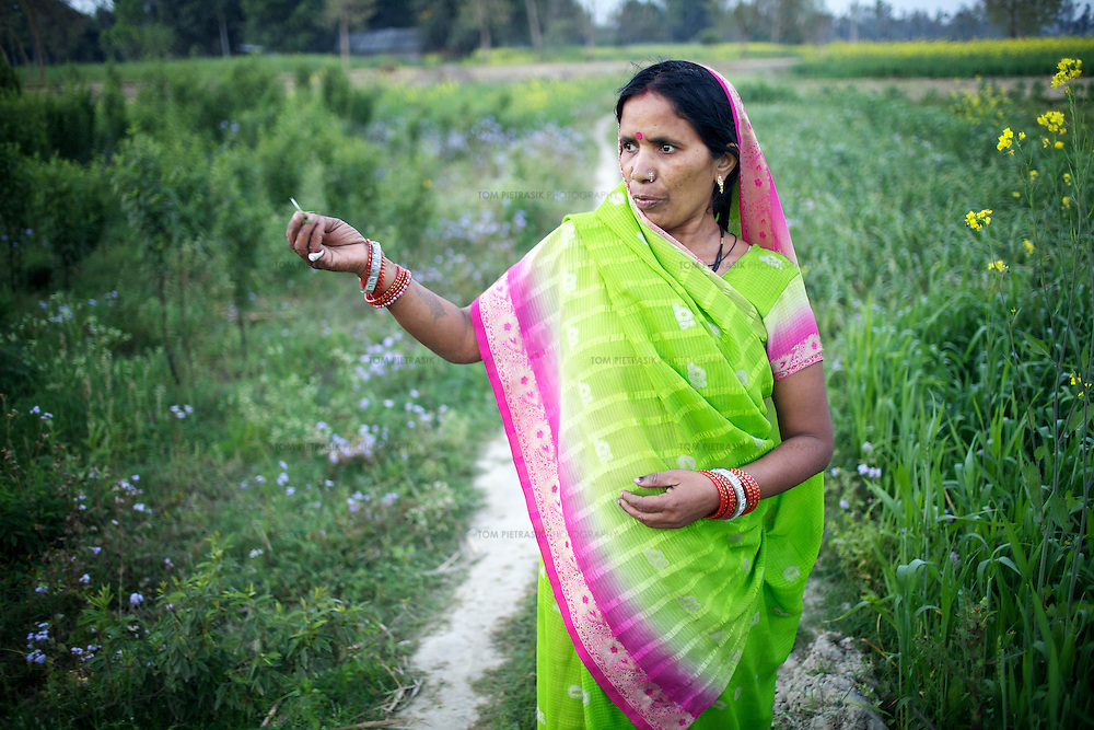Rajkumari Moira walks through fields growing wheat and pulses close to her home in Deramunshi village.<br /> <br /> Rajkumari Moira, 45, from the Maurya caste, has four children, and lives in Deramunshi village. She is frustrated that women do all the domestic work and then labour on land for which they have no title, &ldquo;Women do all the household work; they bring up the children, take care of the family and do agricultural work as well. But if there is not joint entitlement to the land, it&rsquo;s a big risk. If the husband is good, then things are fine; but if he&rsquo;s a drunkard or there is a bad person, it&rsquo;s a high risk. And we don&rsquo;t have security of land or anything to help us.&rdquo; She describes her own husband as a good man. On their one bigha (1,300 sq metro) of land, Rajkumari and her family grow vegetables like cauliflower, tomato, okra and potato, <br /> <br /> &ldquo;Since we have only a small plot of land, we grow vegetables because we can sell them and get higher prices. We buy grains with the money. I can normally make about 10,000 rupees profit each year.  If we grew grains, we would earn about 6-7,000 rupees each year. <br /> <br /> In the north Indian state of UP (Uttar Pradesh), women are responsible for 70 to 80 percent of agricultural work but their contribution remains neglected at all the levels: family, social, economic and policy. Over three quarters of UP's households are involved in farming of which 91% percent operate on land that is marginal and small. Small and marginal farmers often lack access to major agricultural services, such as credit, extension, insurance, and markets.<br /> <br /> On October 15, 2005 a movement called AROH was launched campaigning for the recognition of women as farmers. A federation of women farmers popularly known as &ldquo;Aroah Mahila Kissan Manch&rdquo; has been formed in all the districts of Uttar Pradesh. AROH has begun lobbying the UP government for women to be registered as joint ow
