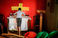 A young man prepares the altar for worship at the Eila rubber plantation in the Sabaragamuwa Province of Sri Lanka on Sunday, Jan. 21, 2018. LCMS Communications/ Erik M. Lunsford