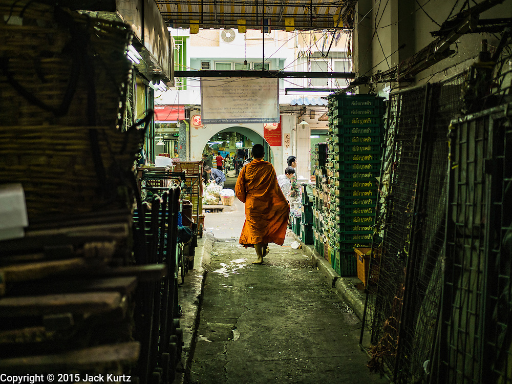 """21 DECEMBER 2015 - BANGKOK, THAILAND: A Buddhist monk leaves Pak Khlong Talat, also called the Flower Market, after his morning alms round. The market has been a Bangkok landmark for more than 50 years and is the largest wholesale flower market in Bangkok. A recent renovation resulted in many stalls being closed to make room for chain restaurants to attract tourists. Now Bangkok city officials are threatening to evict sidewalk vendors who line the outside of the market. Evicting the sidewalk vendors is a part of a citywide effort to """"clean up"""" Bangkok.       PHOTO BY JACK KURTZ"""