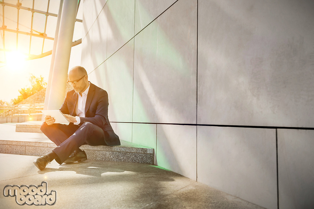 Portrait of businessman using digital tablet while sitting outside the office