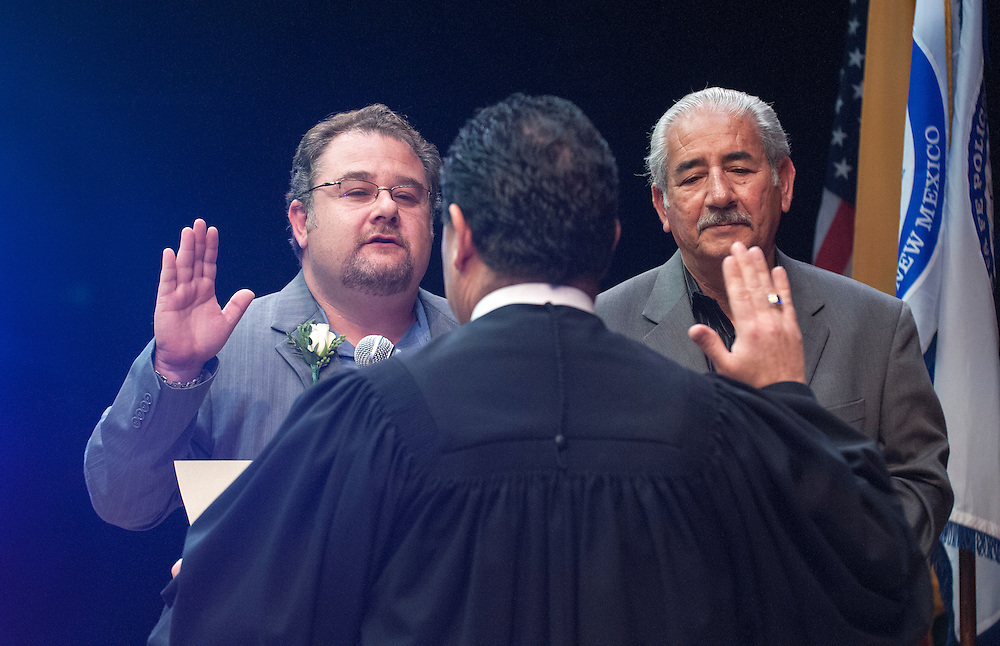 em031014o/a1/Santa Fe City Councilor Carmichael Dominguez, left, is sworn in by Magistrate Judge George Anaya Jr., Monday March 10, 2014. Eddie Moore/Albuquerque Journal