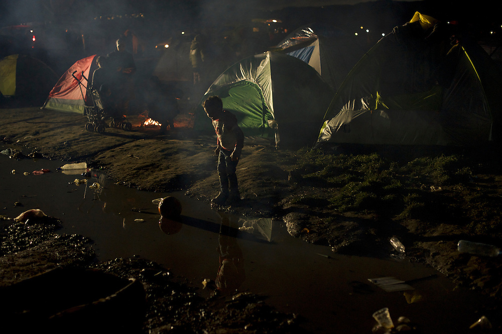 A migrant child plays in dirty water surrounding tents at the Greek-Macedonian border station of Idomeni, Greece. Around 13,000 migrants and refugees, mostly from the Middle East and African nations, are believe to be stranded here awaiting a chance to proceed their journey towards Germany and other northern European countries.