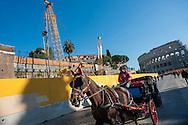 Una carrozzella a cavallo su via dei Fori Imperiali, sullo sfondo il cantiere della Metro C e il Colosseo.