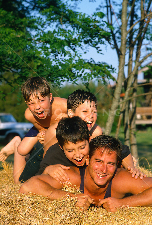 Three boys playfully piled up on man's back in a haystack