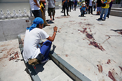 © Licensed to London News Pictures. 15/05/2014. A PDRC protestor takes photos of the blood stains at the site of a grenade and gun shots attack at Democracy monument in Bangkok on May 15, 2014. Grenade blasts and gunfire rocked an anti-government protest site in Thailand's capital, leaving two dead and 24 wounded as fears of wider political violence mounted in Bangkok Thailand. Photo credit : Asanka Brendon Ratnayake/LNP