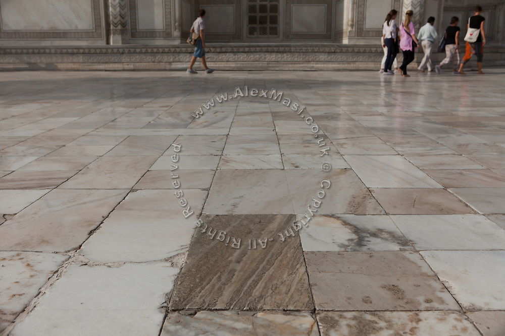 Visitors are walking inside the Taj Mahal complex, in Agra, where a stone seems to have been damaged or even replaced.