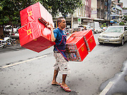 "26 AUGUST 2013 - BANGKOK, THAILAND:    A man carries coffins to be burned in Hungry Ghost Month rituals through the streets of Bangkok. The seventh lunar month (August - September in 2013) is when the Chinese community believes that hell's gate will open to allow spirits to roam freely in the human world for a month. Many households and temples will hold prayer ceremonies throughout the month-long Hungry Ghost Festival (Phor Thor) to appease the spirits. During the festival, believers will also worship the Tai Su Yeah (King of Hades) in the form of paper effigies which will be ""sent back"" to hell after the effigies are burnt.    PHOTO BY JACK KURTZ"