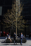 Two associates shake hands after meeting beneath a spring tree on Lime Street in the City of London, the capital's financial district also known as the Square Mile, on 6th April 2017, in London, England.