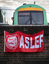 © Licensed to London News Pictures. 14/12/2016. London, UK. A train driver looks out from his cab near a picket line at the entrance to the Selhurst rail depot. Hundreds of thousands of rail passengers face a second day of a 3 day rail strike in an escalating dispute over the role of conductors and drivers. Photo credit: Peter Macdiarmid/LNP
