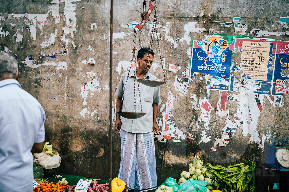 A vegetable seller at a small streetside market in downtown Kandy, Sri Lanka, Asia