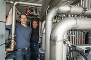 Kaare Gether (t.v.) og Helge Skarphagen i Gether AS ved sirkulasjonssentralen til Mære II, det vil si anlegget som skal drifte energieffektiviseringen ved hele Mære Landbruksskole, nå når pilotanlegget i tomatdrivhuset har viste seg å være en suksess.