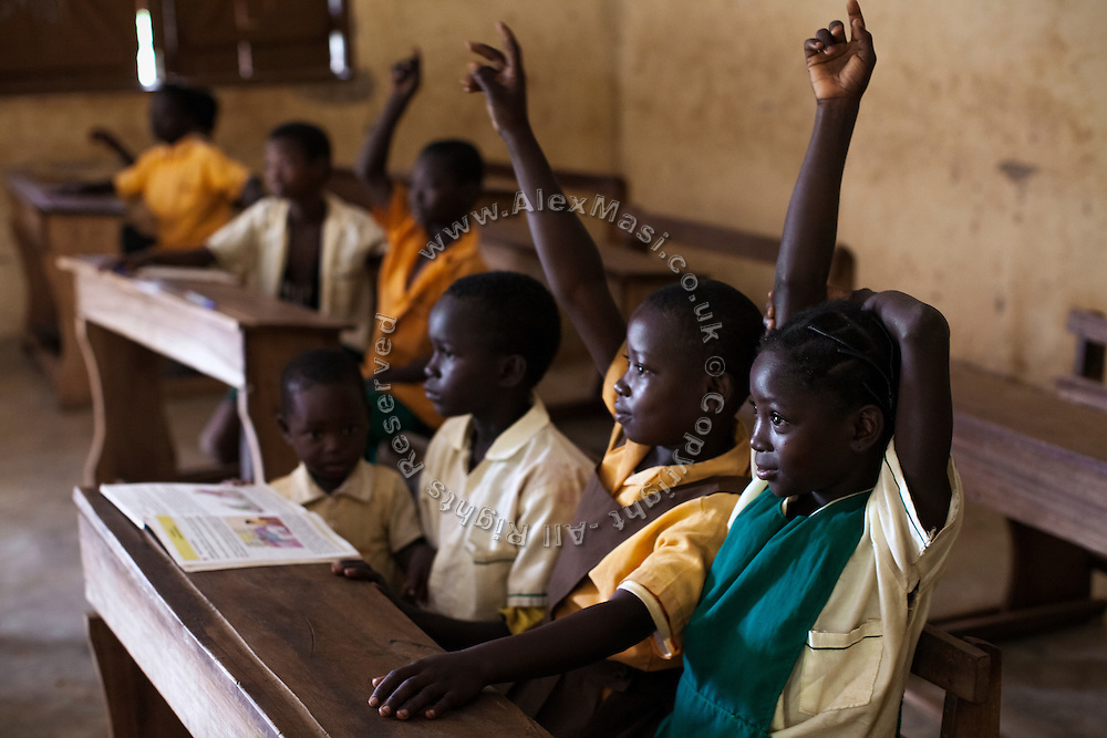 Hassana Ibrahim, 11, (right) is raising her hand in order to answer the teacher's question while sitting in her classroom in Boggu, Tamale, northern Ghana.