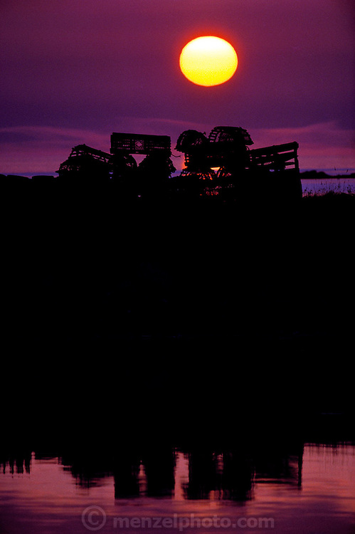 Cape Sable Island, Clark's Harbor. Lobster traps in silhouette, on the dock with setting sun. Nova Scotia, Canada.