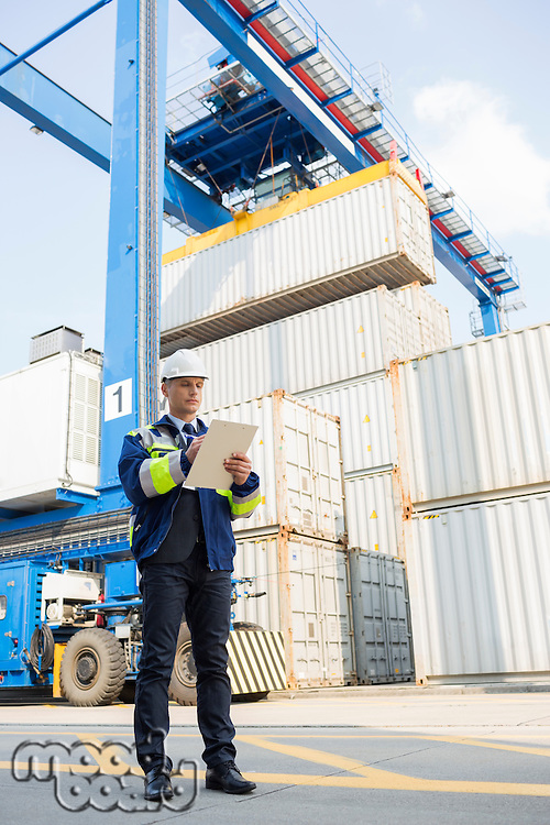 Full-length of male supervisor writing on clipboard in shipping yard