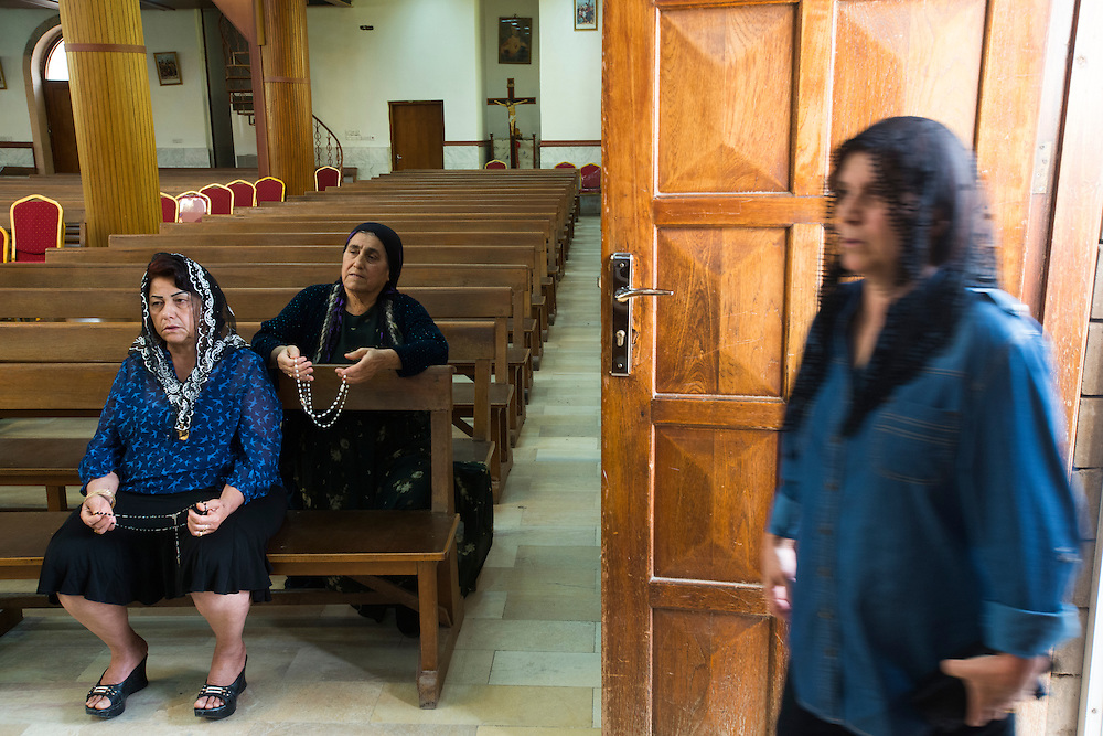 Women praying at the Saint Joseph Chaldean church. The majority of Iraq's Christians belong to the Chaldean Catholic church. Iraq's Christian community is considered one of the longest continues Christian communities in the world. In 2003 there were an estimated 1.5 million Christians in Iraq. Today, Iraqi Christians are thought to number approximately 400,000. Violence, persecution and sectarian strife have forced more than two thirds of the Christian population to flee the country.  Ainkawa, Iraq. 17/04/2014.