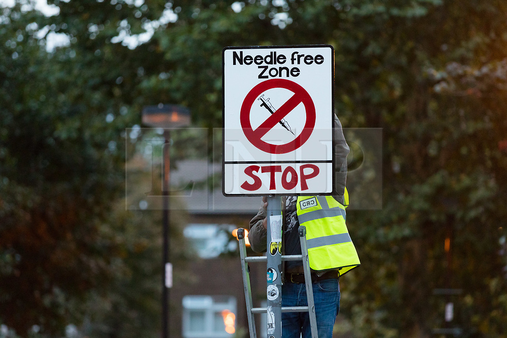 © Licensed to London News Pictures. 16/09/2018. London, UK.  Community activists erect hoax street signs in residential streets near Columbia Road, east London this morning to highlight the high levels of drug dealing, where the cheapest heroin in Europe can allegedly be purchased. The anti drugs street art campaign called the 'Columbia Road Cartel' has been commissioned by the Weavers Community Action Group in Shoreditch, Tower Hamlets. Photo credit: Vickie Flores/LNP