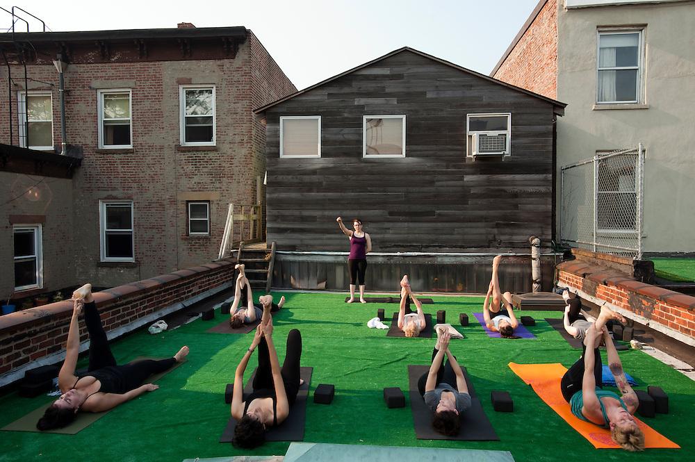 Rebekah Nagy unterrichtet Yoga auf dem Dach des GOOD YOGA in Greenpoint, Brooklyn. Nach dem Unterricht wird unten im Haus fuer 7 Dollar vegetarisches Fruehstueck angeboten..(Yvonne Adamek vorne rechts)..Yoga in New York..Foto: Stefan Falke