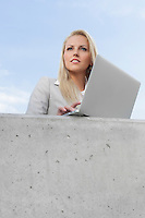 Young thoughtful businesswoman with laptop looking away while standing on terrace against sky