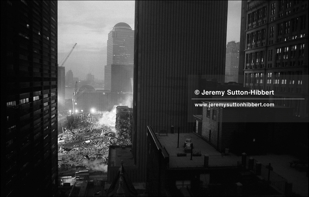The smouldering remains of the World Trade Centre complex in lower Manhattan, destroyed on September 11th 2001 by AL-Qaeda terrorists. Workers clear the site of debris in the search for the bodies of victims. New York, America.