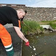Nederland Den Haag 13 mei 2009 20090513 Foto: David rozing .Nieuwbouwwijk Wateringse Veld, medewerkers schoonmaak dienst vissen afval uit het water. opruimen,. opruimdienst, net, netten, visnet, schone omgeving, woonomgeving, sloot, watergang,   Foto: David Rozing/