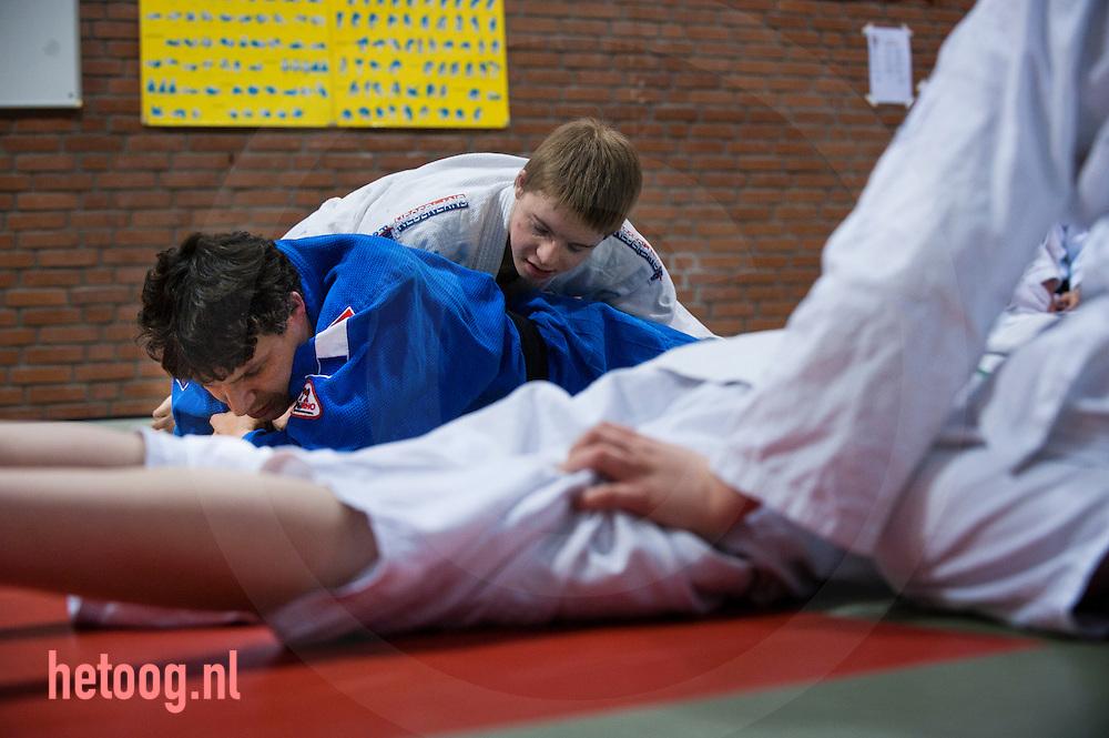 nederland,deventer,11april2012 judo voor kinderen met een beperking Assistent van trainer Gerben Koops,  Mario (blauw pak)