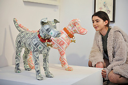 "© Licensed to London News Pictures. 06/10/2017. London, UK.  A visitor views ""George"" and ""Ernesto"", two dog statues covered in US Dollars and Cuban Pesos respectively, both by Justine Smith at the Moniker Art Fair, the world's biggest urban art fair, taking place at the Old Truman Brewery in East London from 5 to 8 October 2017.  The fair brings together the world's most influential new-contemporary and urban art galleries to show international artworks to Londoners. Photo credit : Stephen Chung/LNP"
