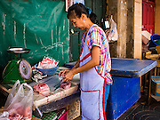 26 FEBRUARY 2016 - BANGKOK, THAILAND: A woman sells fresh meat in front of an abandoned shophouse in the Verng Nakorn Kasem neighborhood. Verng Nakorn Kasem, also known as the Thieves' Market, was one of Bangkok's most famous shopping districts. It is located on the north edge of Bangkok's Chinatown district, it grew into Bangkok's district for buying and selling musical instruments. The family that owned the land recently sold it and the new owners want to redevelop the famous area and turn it into a shopping mall. The new owners have started evicting existing lease holders and many of the shops have closed. The remaining shops expect to be evicted by the end of 2016.      PHOTO BY JACK KURTZ