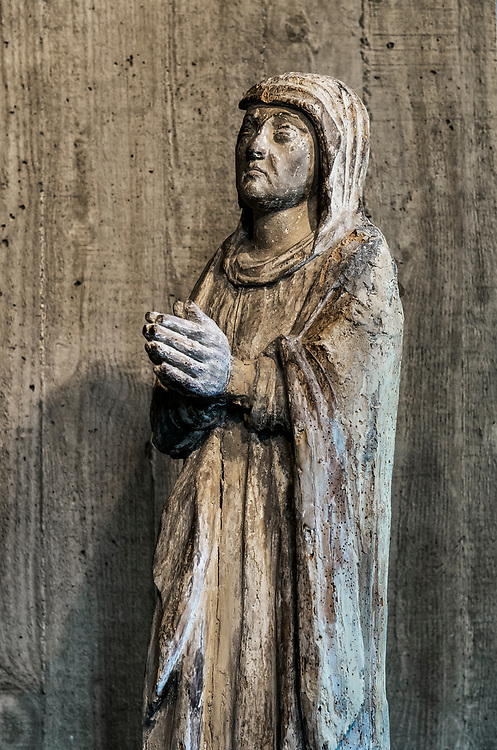Ancient christian religious sculpture of a prayerful believer.