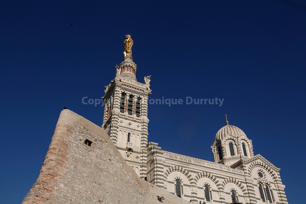 "Notre-Dame de la Garde is a Neo-Byzantine church is situated at the highest natural point in Marseille, a 162 m (532 ft) limestone outcrop on the south side of the Old Port. As well as being a major local landmark, it is the site of a popular annual pilgrimage every Assumption Day (August 15). Local inhabitants commonly refer to it as la bonne mere (""the good mother"")..A minor basilica of the Catholic church, it is situated on a limestone peak of 149m (490 feet), on the walls and foundations of an old fort. Built by architect Henri-Jacques Esperandieu in the Neo-Byzantine style, the basilica was consecrated on 5 June 1864. The  church is of Neo-Byzantine style decorated with mosaics. A square bell-tower of 41m (135 feet) is surmounted by a belfry of 12.5m (42 feet) which itself supports a monumental, 11.2m (27 feet) tall statue of the Madonna and Child made out of copper gilded with gold leaf"